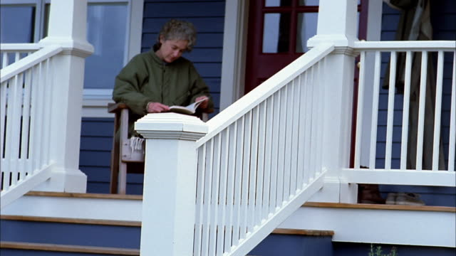medium shot woman reading on front porch and looking up / bainbridge island, washington - front porch stock videos and b-roll footage