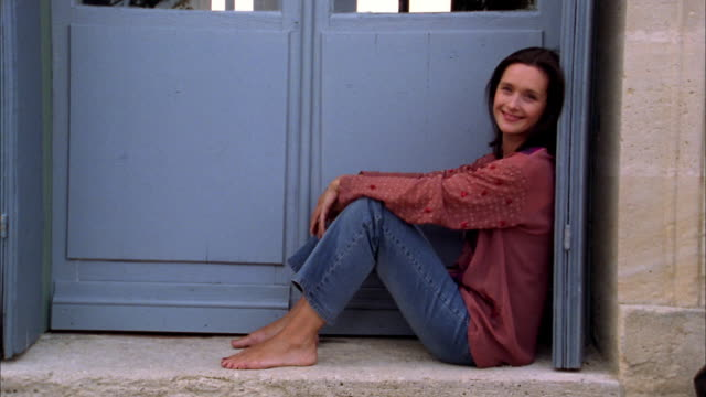 Medium shot woman resting against wall outside front door and smiling at CAM