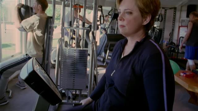 medium shot woman riding exercise bike in gym/ solebury, pennsylvania - 中年の女性一人点の映像素材/bロール