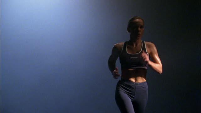 vídeos y material grabado en eventos de stock de medium shot woman running in place against blue background - corredora de footing