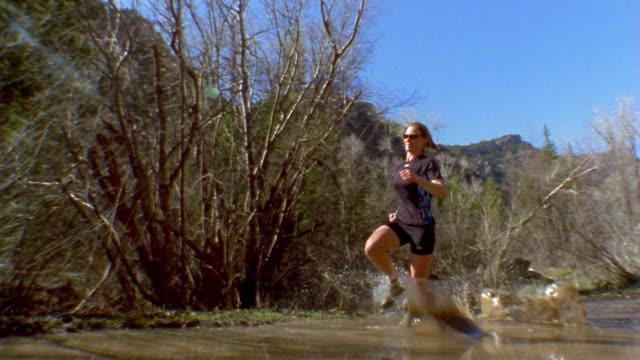 medium shot woman running through muddy water w/trees in background / colorado, usa - lycra stock videos & royalty-free footage
