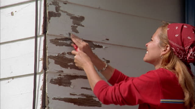 medium shot woman scraping paint off house - scraping stock videos and b-roll footage