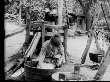 vidéos et rushes de 1910 b/w medium shot woman scrubbing laundry in yard when dapper man approaches from road  - 1900 1909