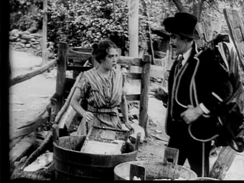 stockvideo's en b-roll-footage met 1910 b/w medium shot woman scrubbing laundry in yard when dapper man approaches from road  - 1900 1909