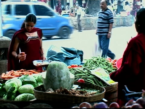 Medium shot woman selecting carrots at produce stand / handing tray to vendor to be weighed