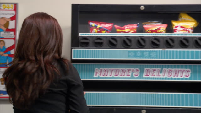 vidéos et rushes de medium shot woman shaking vending machine / knocking vending machine over / los angeles - machinerie