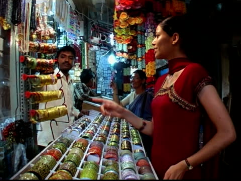 medium shot woman shopping for bracelets at jewelry stand at market / vendor handing her bangle to try on - bangle stock videos & royalty-free footage