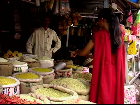 stockvideo's en b-roll-footage met medium shot woman shopping for grains at market stall / vendor pointing out his wares - mid volwassen mannen