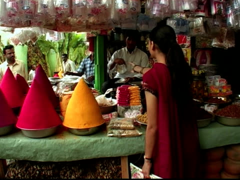 Medium shot woman shopping for tins at stand with mounds of colored powder