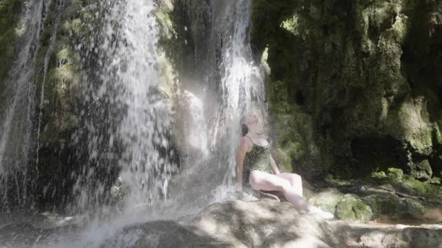 vídeos y material grabado en eventos de stock de medium shot, woman sits under waterfall in krka national park - catarata