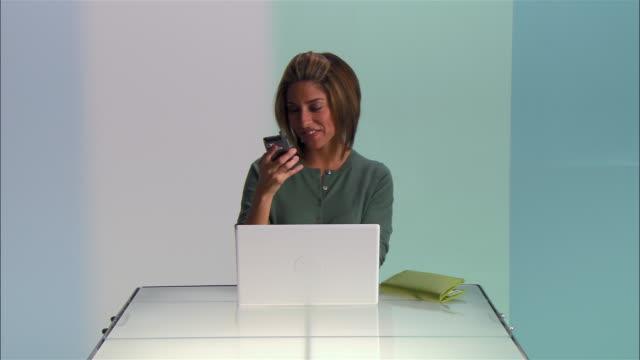 medium shot woman sitting at desk, typing on laptop - electronic organiser stock videos & royalty-free footage
