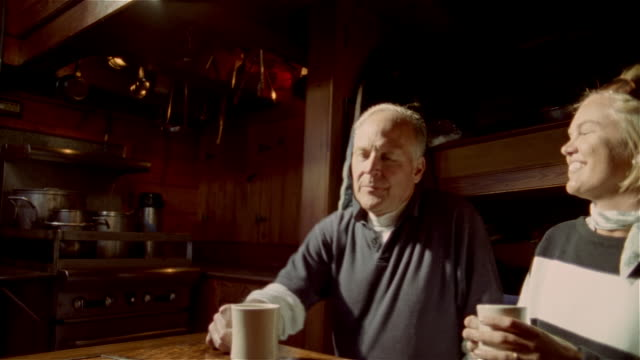 vídeos de stock e filmes b-roll de medium shot woman sitting in galley of tall ship / man sitting down with mugs / talking and drinking hot beverages - sentar se