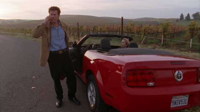 medium shot woman sitting in red convertible as man stands outside car talking on cell phone/ napa valley, california - vehicle breakdown stock videos and b-roll footage