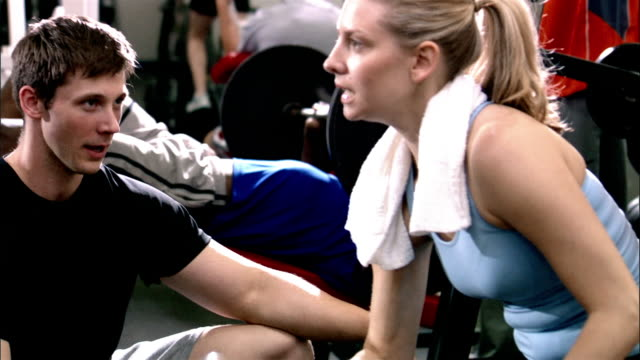 medium shot woman sitting, lifting weight/ trainer walking in and crouching down/ pan behind column/ trainer talking to woman and nodding/ trainer getting up and leaving - health club stock videos & royalty-free footage