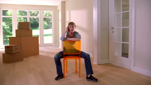 Medium shot woman sitting on orange chair in empty room and talking on cellular phone w/boxes in background