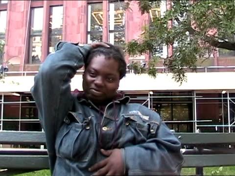vídeos de stock, filmes e b-roll de medium shot woman sitting on park bench, rubbing stomach and patting head/ new york city - só uma mulher de idade mediana
