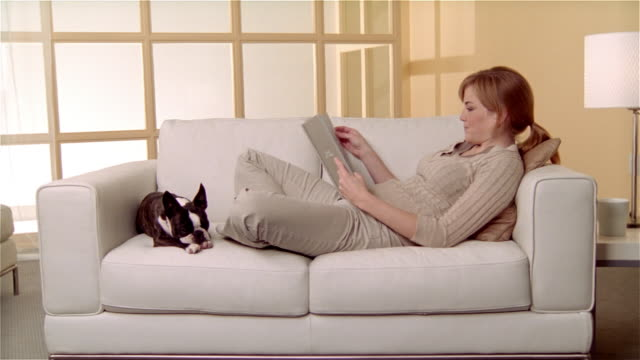Medium shot woman sitting on sofa with Boston Terrier, reading book/ zoom in close up dog