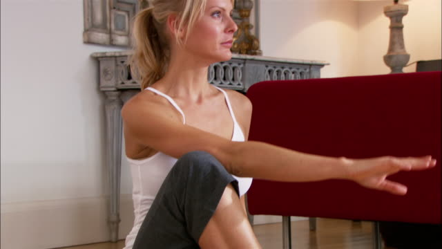 "medium shot woman sitting on wooden floor doing yoga/ tilt up zoom in woman turning into ""seated twist"" position/ close up woman turning, looking toward camera, and smiling/ london - nur junge frauen stock-videos und b-roll-filmmaterial"