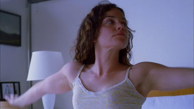 medium shot woman sitting up in bed / stretching and yawning - fare lo stretching video stock e b–roll