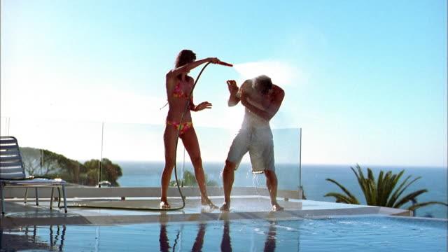 medium shot woman spraying man w/water hose by swimming pool - hose stock videos & royalty-free footage