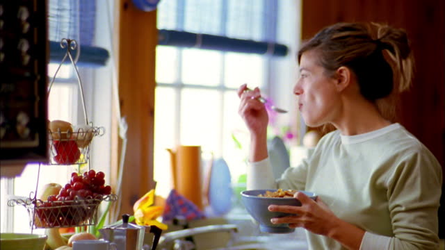 Medium shot woman standing and eating cereal from bowl near kitchen sink + looking out window / turning around