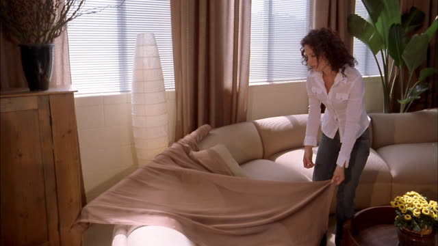 medium shot woman standing and stretching out sheer fabric on living room sofa - インテリアデザイナー点の映像素材/bロール