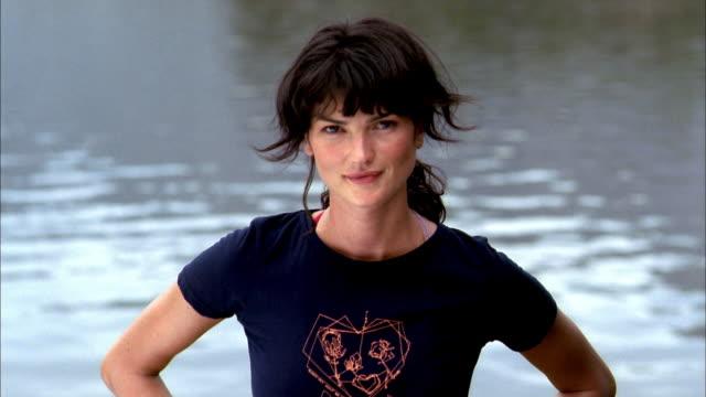 vídeos y material grabado en eventos de stock de medium shot woman standing by lake and looking at cam - mirar fijamente