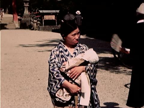 1939 medium shot woman standing on street with baby/ japan - 1930~1939年点の映像素材/bロール