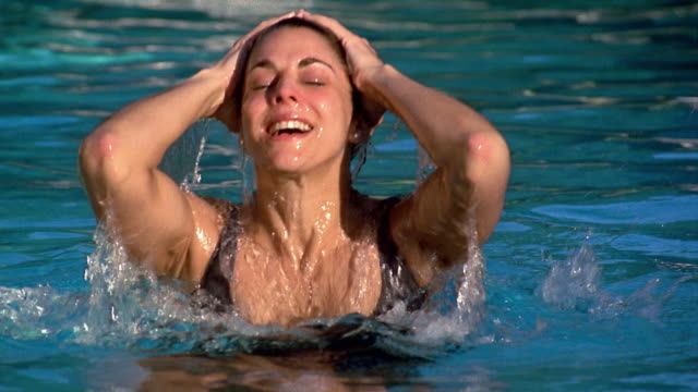 medium shot woman surfacing from water in swimming pool - surfacing stock videos and b-roll footage