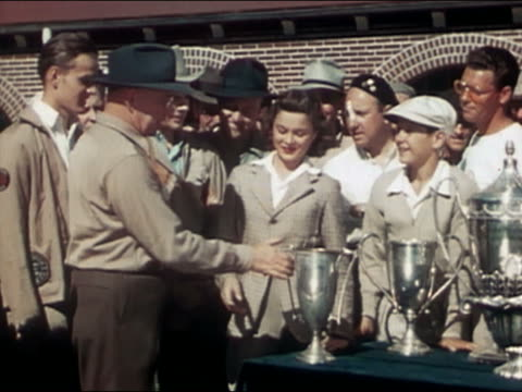 1946 medium shot woman surrounded by men accepting trophy / spectators clapping / audio - auszeichnung stock-videos und b-roll-filmmaterial