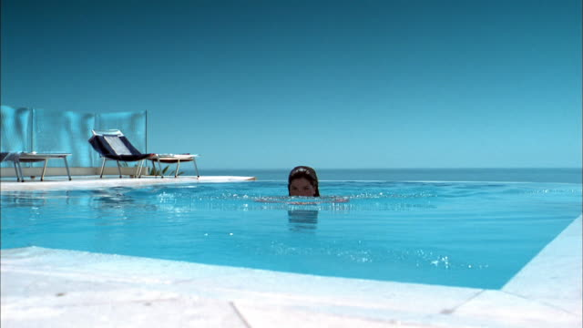 medium shot woman swimming to edge of pool and smiling at cam w/beach chairs in background - infinity pool stock videos & royalty-free footage