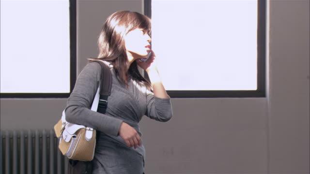 medium shot woman talking on cell phone in front of windows in loft/ brooklyn, new york - solo una donna di età media video stock e b–roll