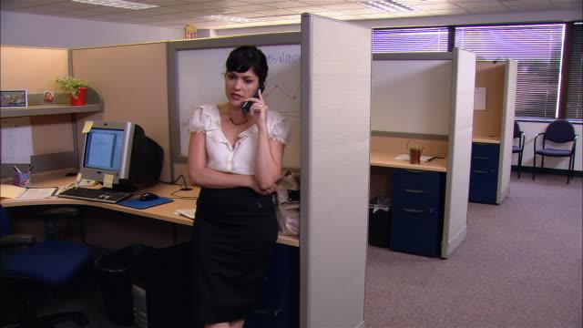 vídeos de stock e filmes b-roll de medium shot woman talking on phone in cubicle - trabalhadora de colarinho branco