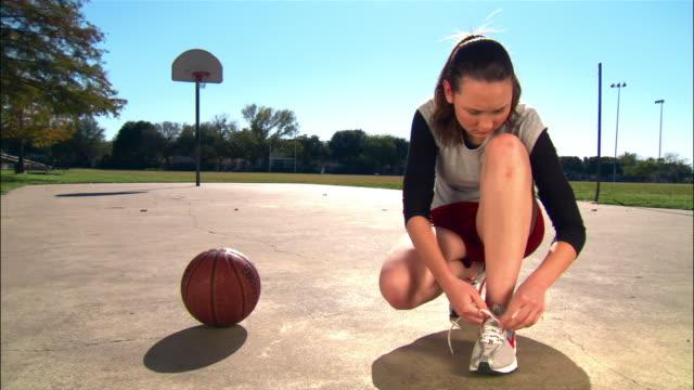 Medium shot woman tying shoes and picking up basketball/ wide shot woman running and shooting baskets/ Dallas, Texas