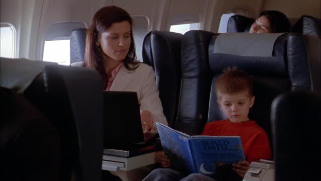 medium shot woman using laptop computer on airplane / young boy reading book - kupe bildbanksvideor och videomaterial från bakom kulisserna
