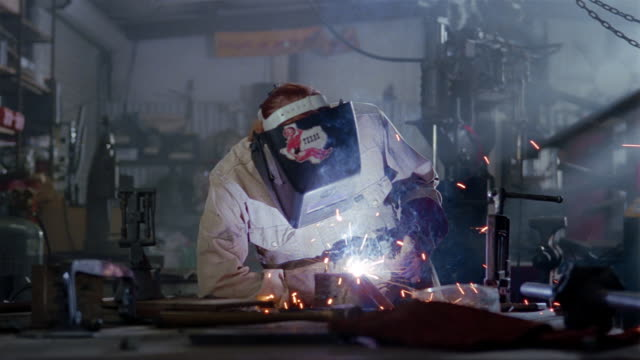vídeos de stock, filmes e b-roll de medium shot woman using welding torch in workshop / standing up and flipping back mask + smiling - soldador