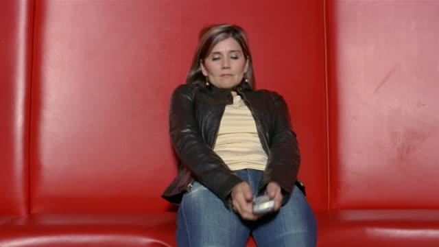 Medium shot woman walking in, sitting down, and laughing while texting on PDA/ San Antonio, Texas