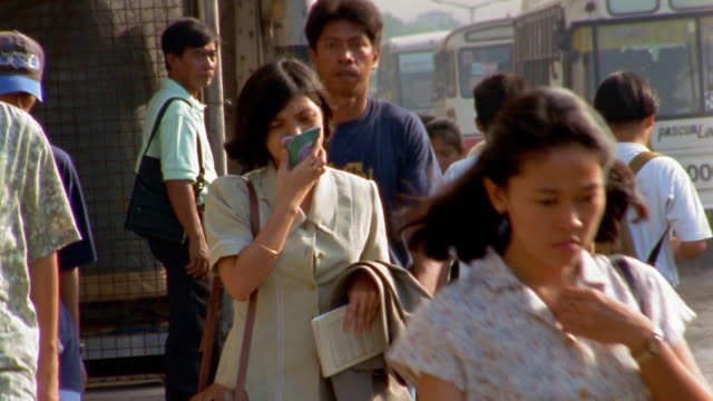 Medium shot woman walking on crowded sidewalk with folded handkerchief covering nose and mouth / Manila
