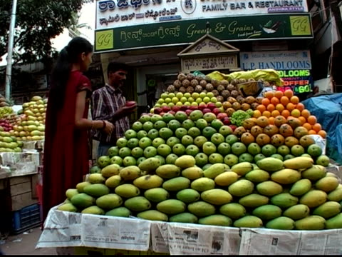 Medium shot woman walking up to produce stand and buying apples from vendor / smelling fruit