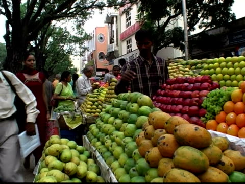 stockvideo's en b-roll-footage met medium shot woman walking up to produce stand and talking to vendor about apples - mid volwassen mannen