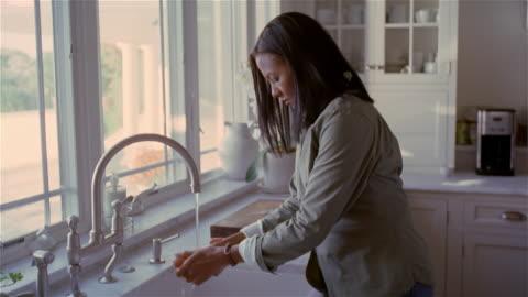 vidéos et rushes de medium shot woman washing carrots in kitchen sink/ solebury, pennsylvania - laver