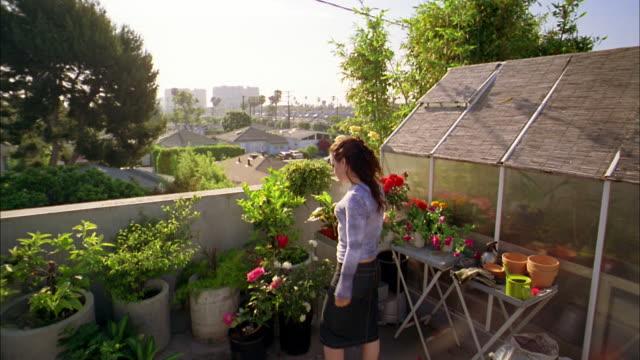 Medium shot woman watering plants on greenhouse terrace w/spray bottle