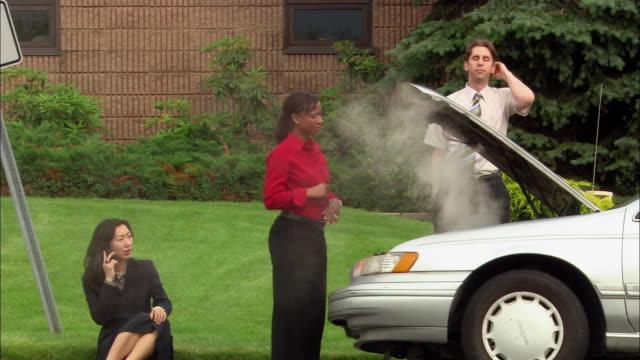 Medium shot woman waving smoke away from hood of broken down car / man walking around front of car and kicking tire / woman sitting on curb talking on cell phone