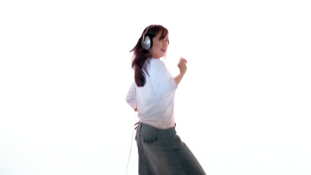 medium shot woman wearing headphones and dancing / england - navel stock videos & royalty-free footage