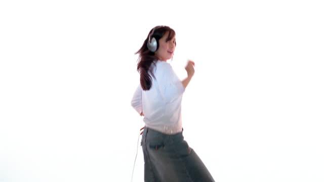 stockvideo's en b-roll-footage met medium shot woman wearing headphones and dancing / england - navel