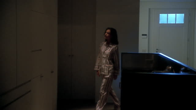 vidéos et rushes de medium shot woman wearing pajamas opening refrigerator and getting midnight snack - minuit