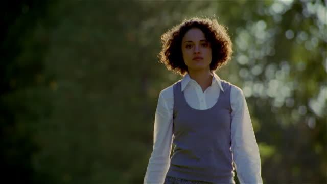 medium shot woman wearing skirt walking towards camera / smiling - 20代点の映像素材/bロール