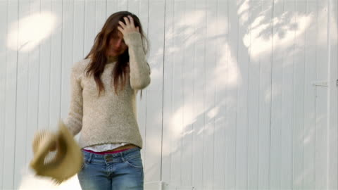 medium shot woman wearing straw cowboy hat standing in front of barn / removing hat and mussing hair / smiling at camera - hat stock videos & royalty-free footage
