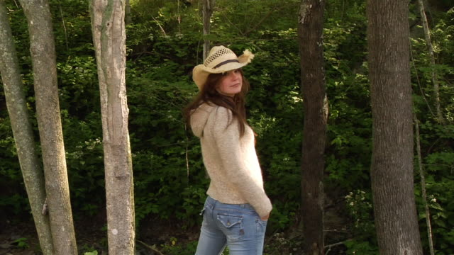 medium shot woman wearing straw cowboy hat standing with back to the camera / looking  over shoulder at camera and removing hat - straw hat stock videos & royalty-free footage