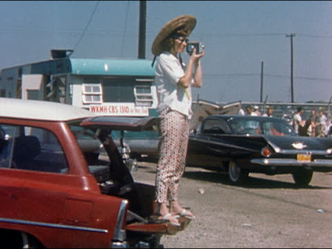 1959 medium shot woman wearing straw hat standing on back of station wagon filming raceway with movie camera - filmkamera stock-videos und b-roll-filmmaterial